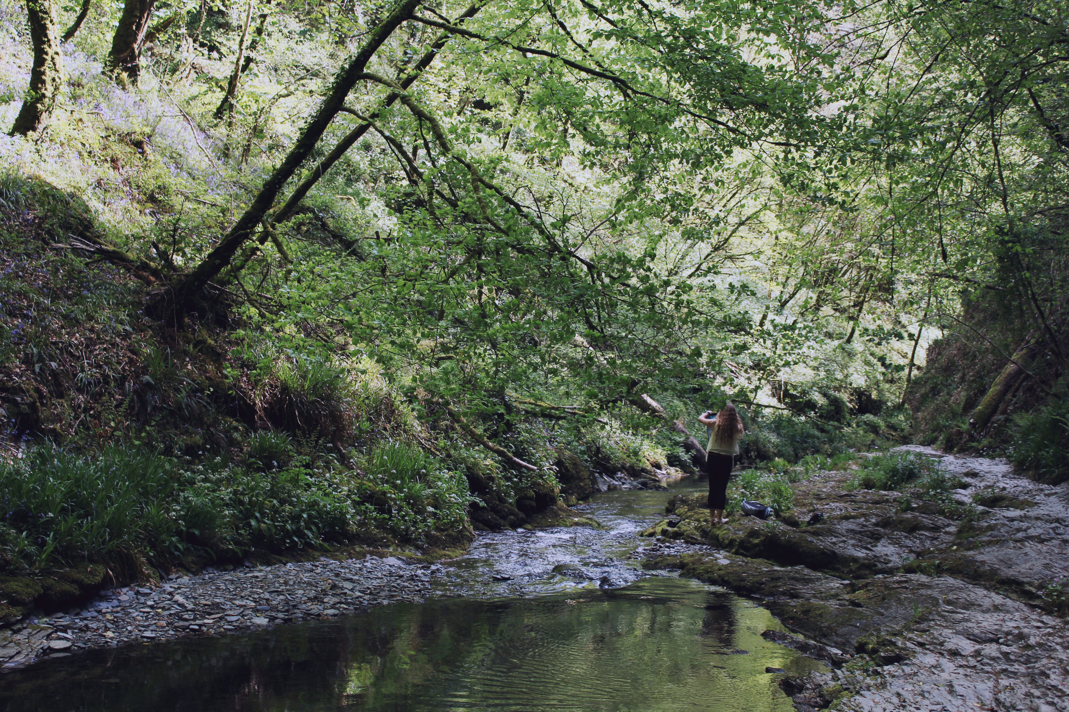 Girl by the river in the forest, at Lydford Gorge, Devon