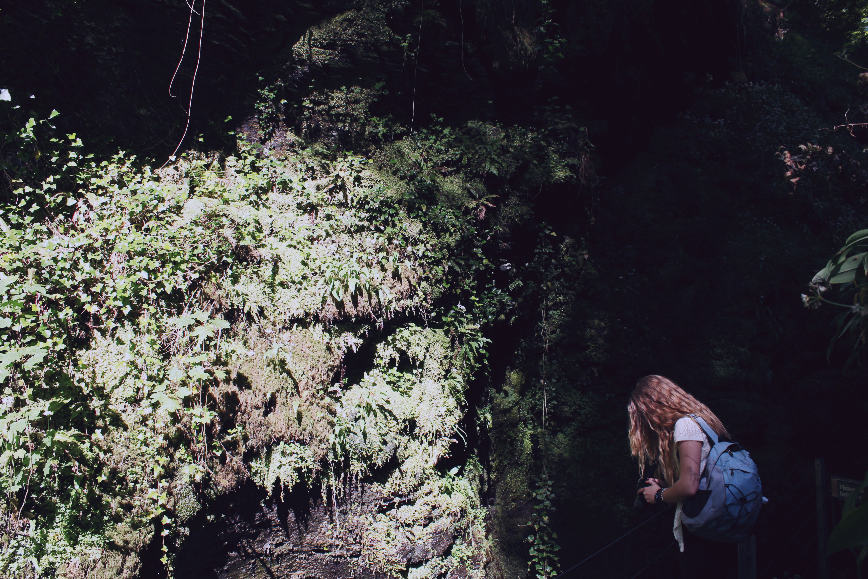 Sarah with a backpack taking a photo at Lydford Gorge, Devon