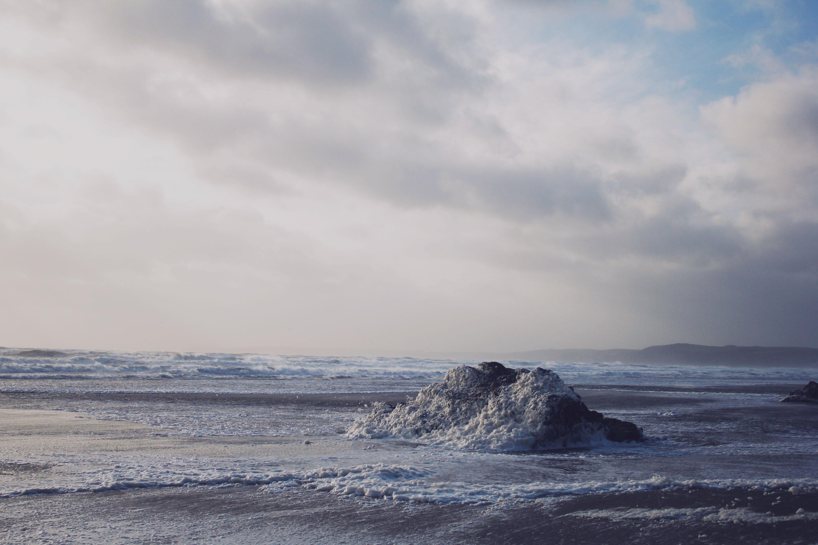 Sea foam on the rocks at Whitsand Bay, Cornwall